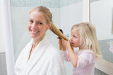 Happy mother and daughter brushing hair