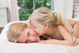 Cute little girl and mother on bed