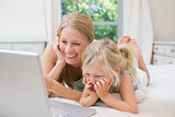 Cute little girl and mother on bed using laptop