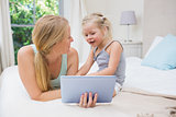 Cute little girl and mother on bed using tablet