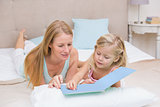 Cute little girl and mother on bed reading