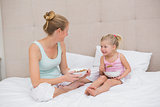 Cute little girl and mother on bed eating cereal