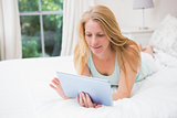Happy blonde using tablet pc on bed