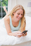 Happy blonde using smartphone on bed