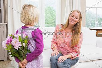 Little girl hiding flowers from mother