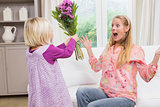 Little girl surprising her mother with flowers