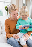Happy mother and daughter on the couch using tablet