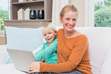 Happy mother and daughter on the couch using laptop