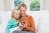 Happy mother and daughter on the couch using smartphone