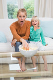 Happy mother and daughter watching tv
