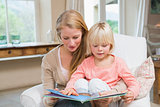Happy mother and daughter reading together