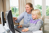 Cute daughter and mother using computer