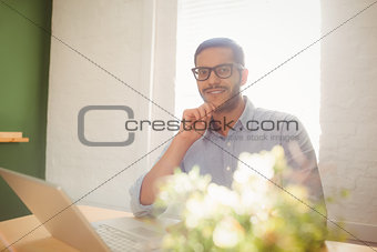 Casual businessman using his laptop at his desk