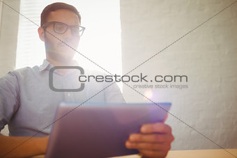 Casual businessman using his tablet at his desk