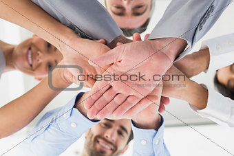 Four workers stacking hands together