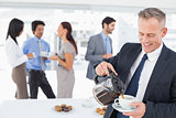 Businessman pouring himself some coffee