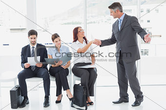 Smiling businessman shaking co-workers hand