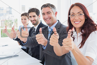 Business team all giving thumbs up