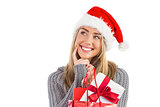Festive blonde holding christmas gift and bag