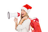 Festive blonde holding megaphone and bags