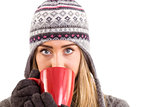 Happy blonde in winter clothes holding mug