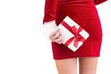 Sexy santa girl holding gift behind back