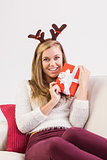 Festive blonde relaxing on sofa with gift