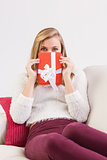 Pretty blonde relaxing on sofa with gift