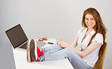 Pretty redhead with feet up on desk
