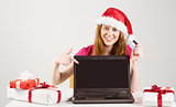 Festive redhead shopping online with laptop