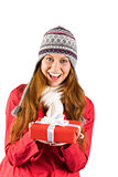 Pretty redhead in warm clothing holding gift