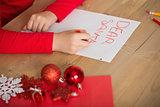 Little girl writing letter to santa at christmas