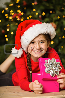 Little girl opening a gift at christmas