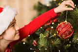 Festive little girl hanging a christmas decoration
