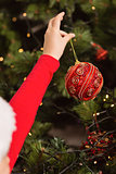 Festive little girl hanging a christmas decoration