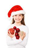 Festive little girl smiling at camera holding baubles