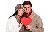 Young couple smiling holding red heart