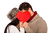 Young couple kissing behind red heart