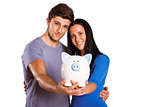 Young couple holding a piggy bank