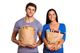 Young couple holding grocery bags