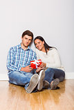 Young couple sitting on floor with gift