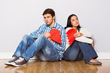 Young couple sitting on floor with broken heart