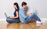 Young couple sitting on floor using laptop