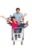 Young couple having fun with shopping cart