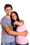 Young couple showing keys to house