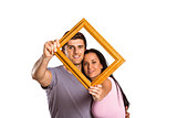 Young couple holding up frame