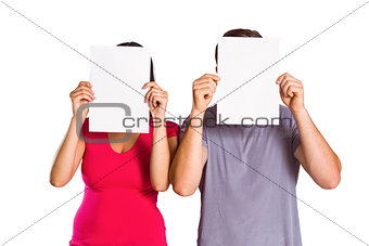 Couple covering faces with paper