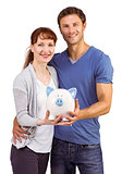 Couple holding a white piggy bank