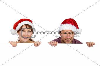Couple both wearing santa hats