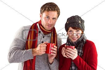 Couple both having warm drinks